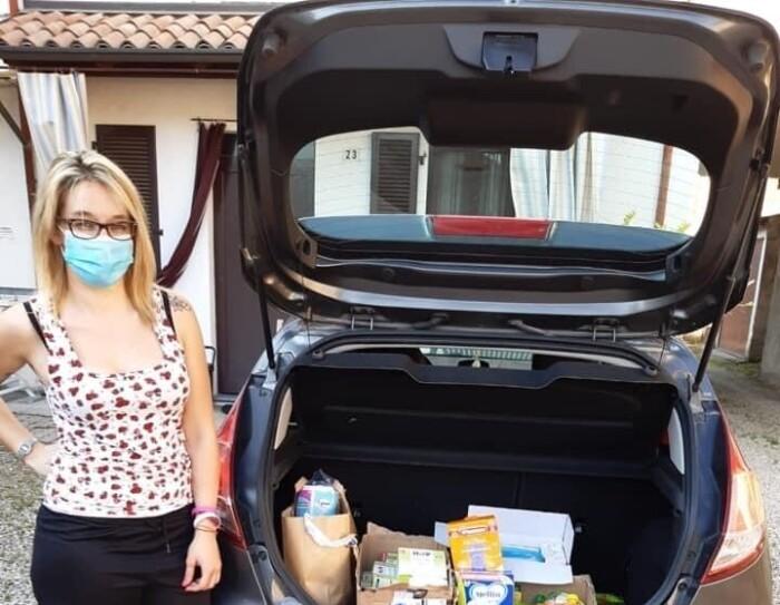 Una donna davanti al baule di un'auto pieno. Indossa una mascherina sul volto e guarda verso la camera.