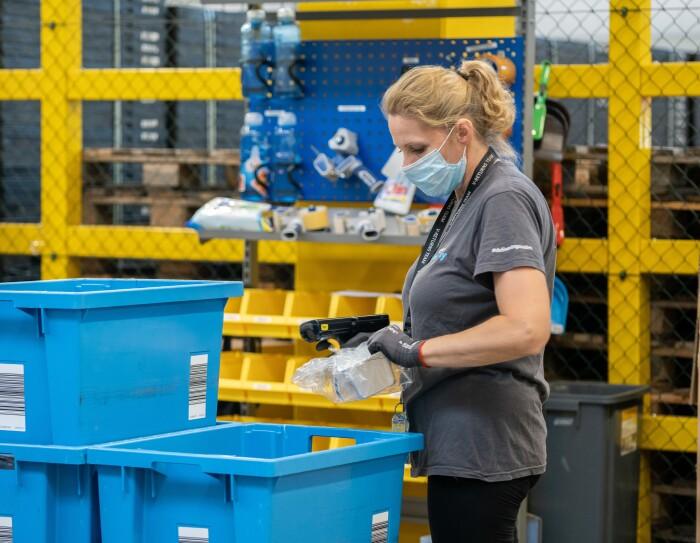 L'immagine mostra una dipendente di amazon all'interno del magazzino che smista i prodotti per spedirli ai liquidatori.