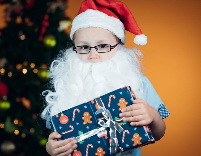 Ein Junge mit Brille, Weihnachtsmann-Mütze und weißem Weihnachtsmann-Bart schaut in die Kamera. Er hält ein blaues Geschenk in den Händen.