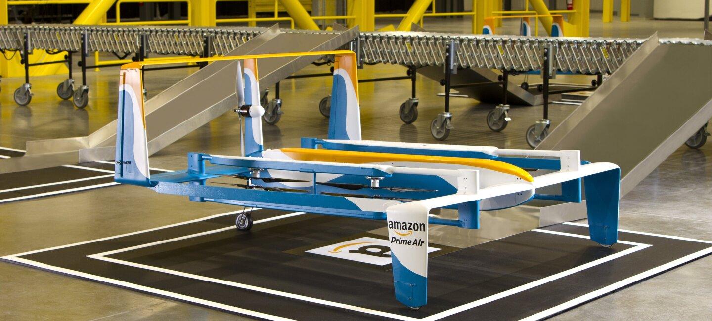 Primer plano del dron de Amazon ubicado en el interior de un centro logístico. El dron es de color blanco, azul y amarillo.