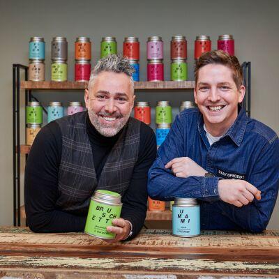 Zwei Männer stehen hinter einer Holztheke und lachen in die Kamera. Sie halten Gewürzdosen mit verschiedenfarbigen Ettiketten in den Händen.