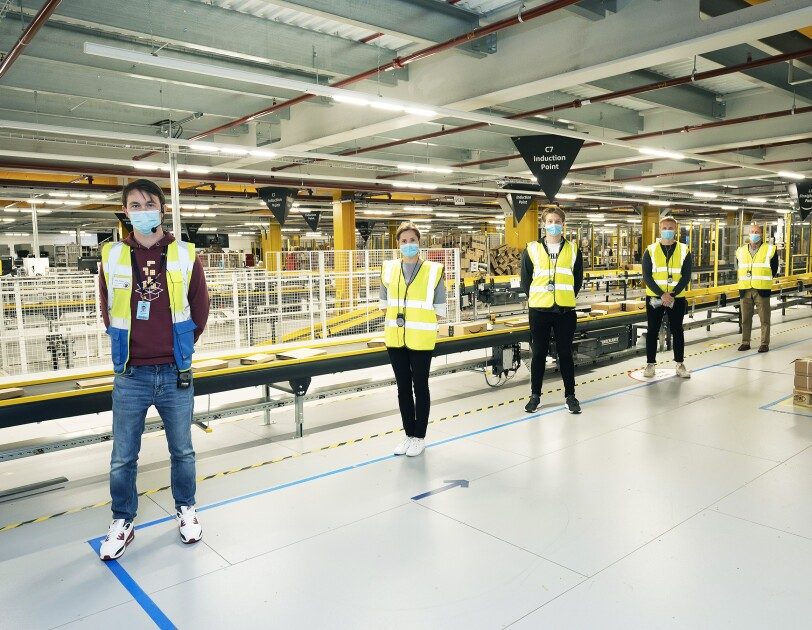 External businesses social distancing on a fulfilment centre tour, they are wearing face masks and yellow hi-vis jackets.