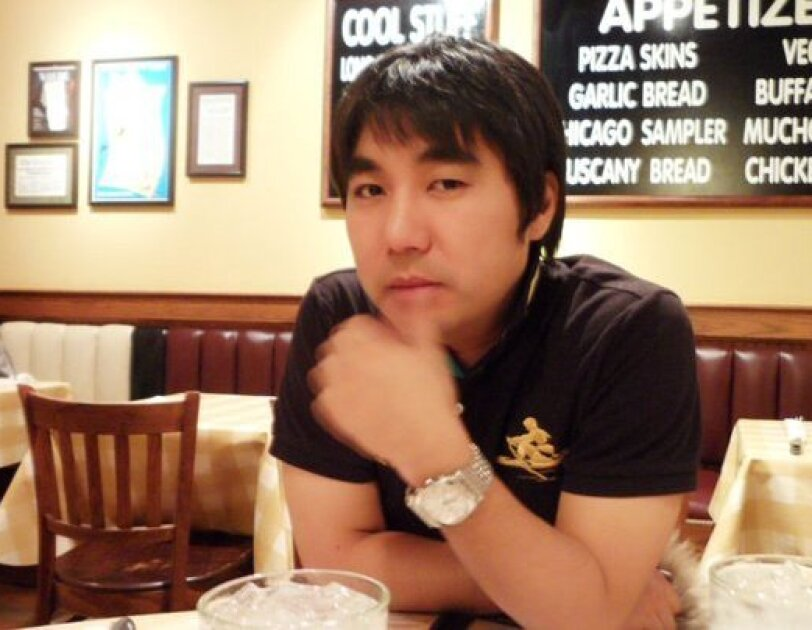 A man, Young-Bum Kim, is seated in a restaurant. He's leaning on one arm, with the other arm crossed, with his hand near his face. In front of him are iced beverages, behind him additional restaurant seating and menu items displayed on the wall.