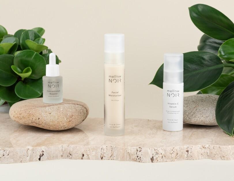 Auf einer Steinplatte stehen drei Produkte von Mellow-Noir. Um sie herum sind Steine und Pflanzen positioniert.