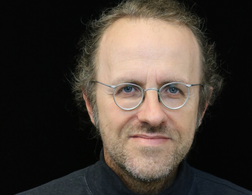 Bernhard Schölkopf, chief machine learning scientist for Amazon's retail division, he wears a black turtle neck and wire framed silver glasses, and sits in front of a black background.