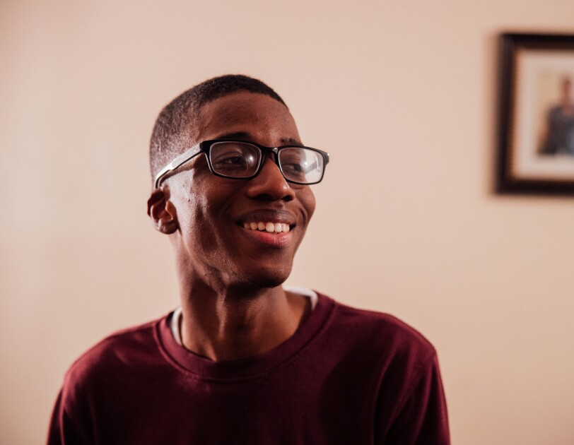 A teenage boy in glasses smiles and looks diagonally away from the camera. A framed photo hangs on the wall in the background.
