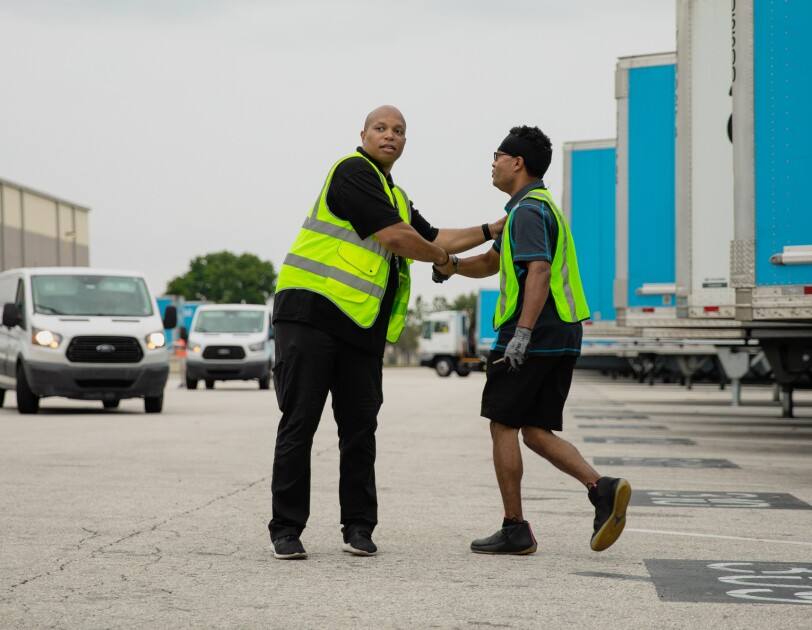 Two men wearing safety vests shake hands. Trucks and vans are in the background.