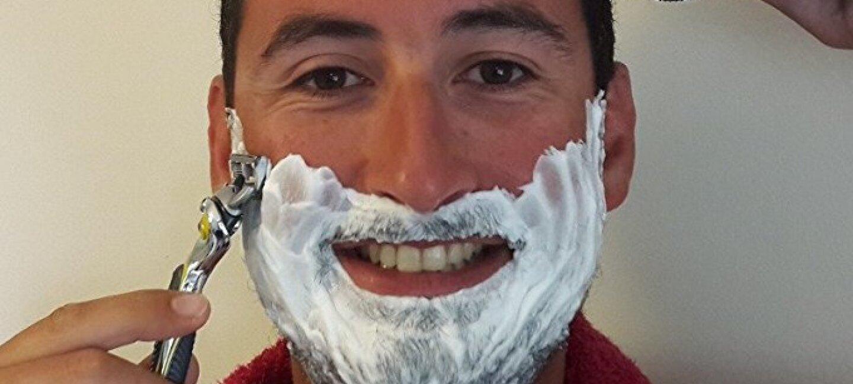Un homme torse nu avec une serviette autour du cou a la barbe couverte de mousse à raser et tient dans chacune de ses mains un rasoir mécanique et un rasoir électrique. Il les tient posés sur ses cheveux et sa barbe en souriant.