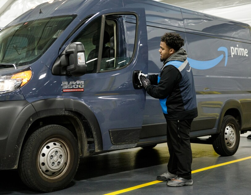 A man uses a disposable disinfecting wipe to clean the driver-side door handle of a van with the Amazon smile logo.