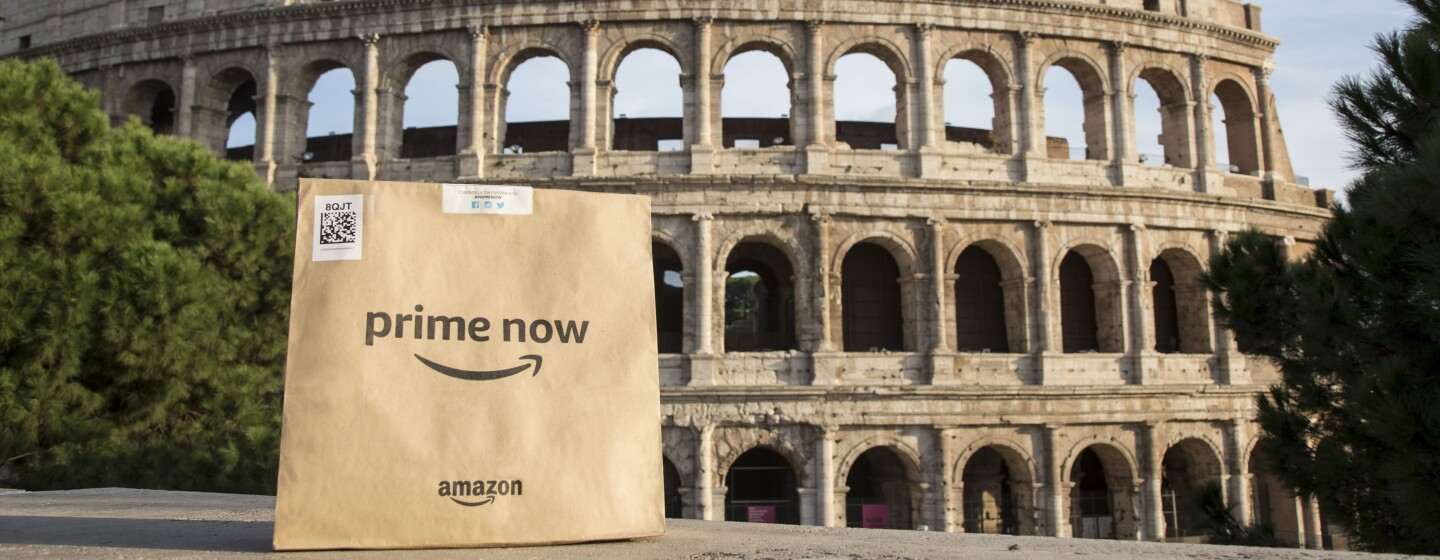 Package with Amazon and Prime Now logo on the front sits across the Colosseum  in Rome.