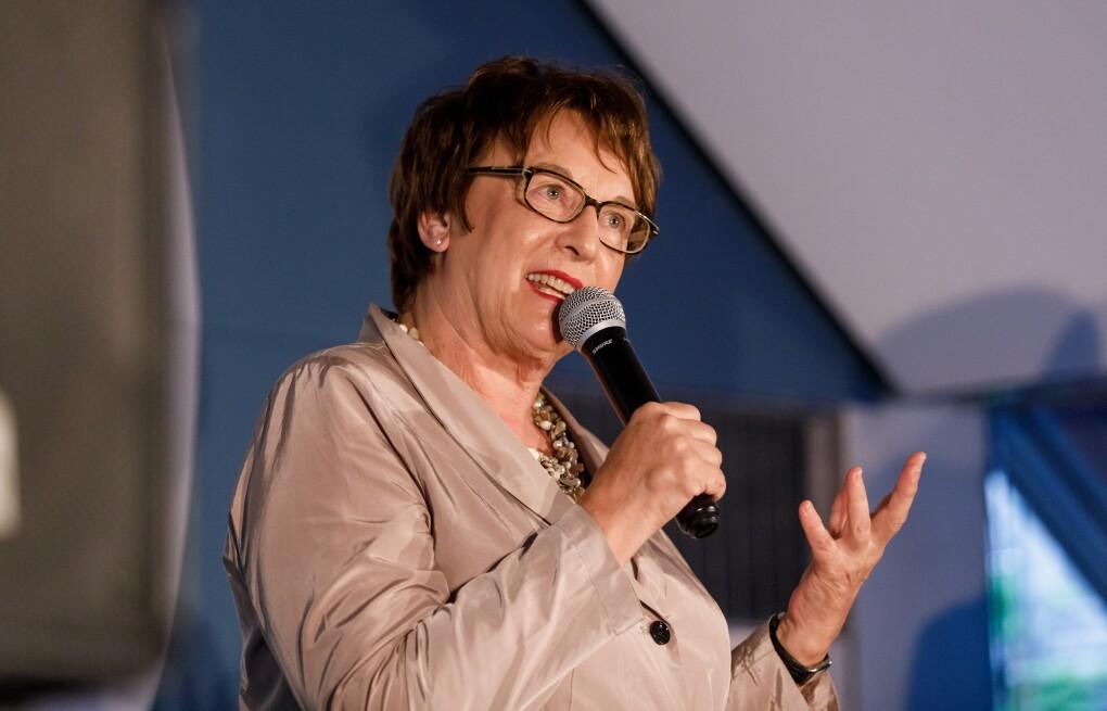 Brigitte Zypries steht auf der Bühne, sie hält ein Mikrofon in der Hand und schaut freundlich ins Publikum