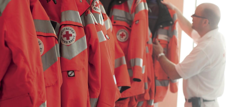 DRK Rettungsdienst Bitburg: Die typischen orangenen Jacken hänngen in einer Reihe. Ein Rettungsdienst Mitarbeiter steht im Hintergrund und zieht sich gerade eine Jacke an.