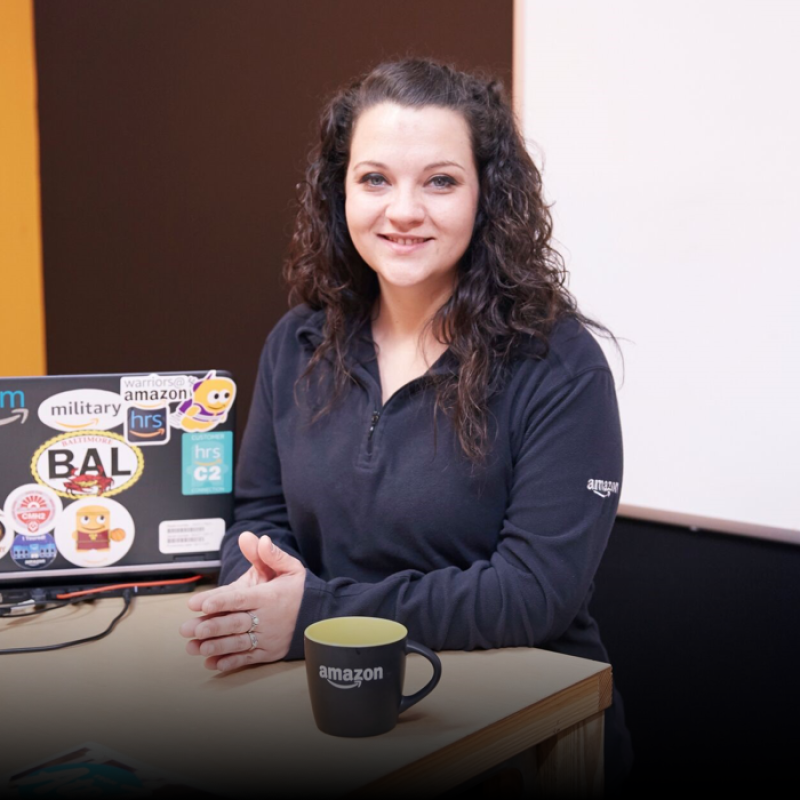 Amazon employee, Autum Becht, stands against a desk next to an Amazon laptop and mug.