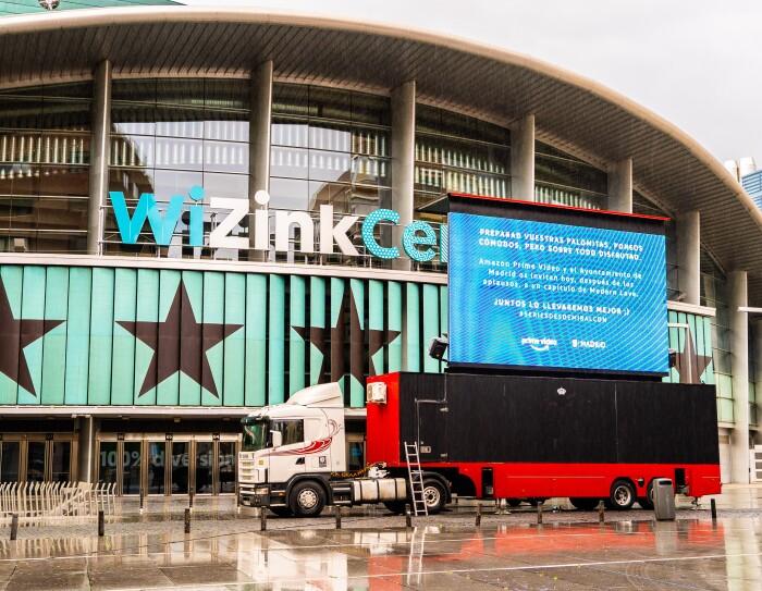 #SeriesDesdeMiBalcón es una iniciativa creada por Amazon Prime Video, el ayuntamiento de Madrid y Exterior Plus. Es la plaza Felipe II de Madrid. De fondo el palacio de deportes Wizink Center. Justo delante un trailer de colo blanco con una caja negra y roja. Encima una pantalla gigante donde se proyecta la serie.