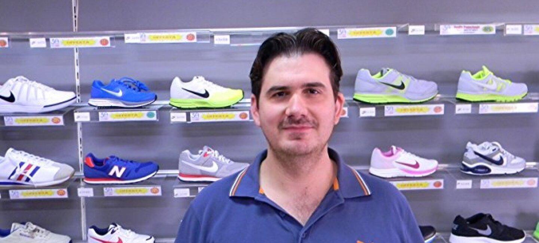 """Ritratto di Cristian Zanatta, giovane commerciante romagnolo, nonché la mente imprenditoriale che si cela dietro il successo del negozio """"Calzature&Sport"""" su Amazon.it. Alle sue spalle, esposizione di scarpe del suo negozio."""