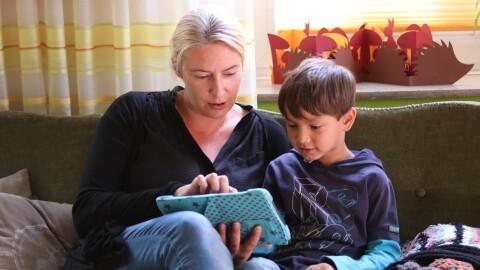 Eine blonde Frau sitzt mit einem Kinder auf einer Couch, beide schauen in ein Tablet.