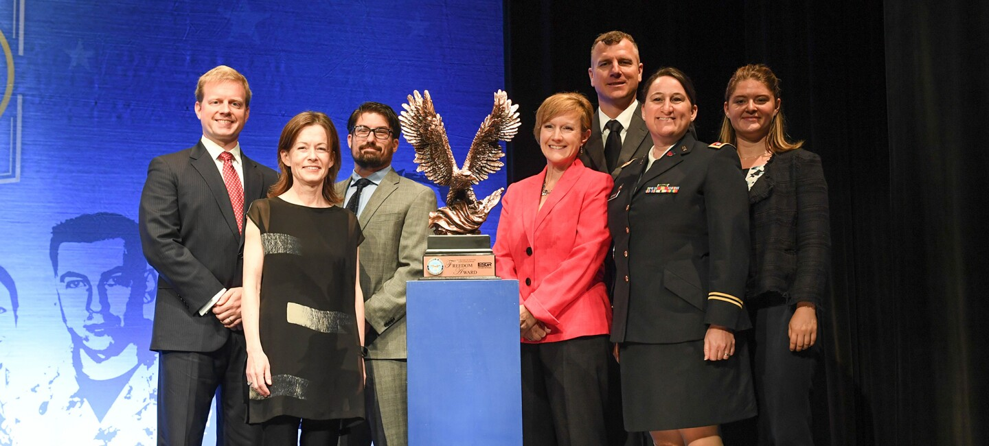 A group of three men and four women stand alongside a metal statue award for the Freedom Award.
