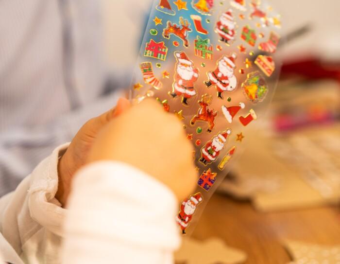 Lucía, hija de Fernando y Marta, tiene tres años. Se ve solo parte desenfocada de la cara de Lucía. Está con las dos manos intentando despegar unas pegatinas de Papá Noel.