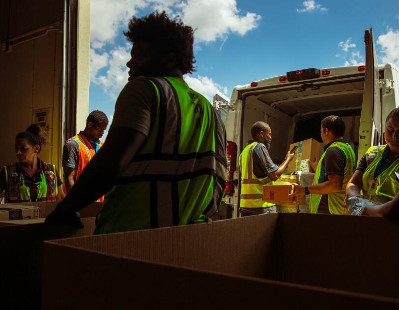 People in safety vests unload a delivery van.