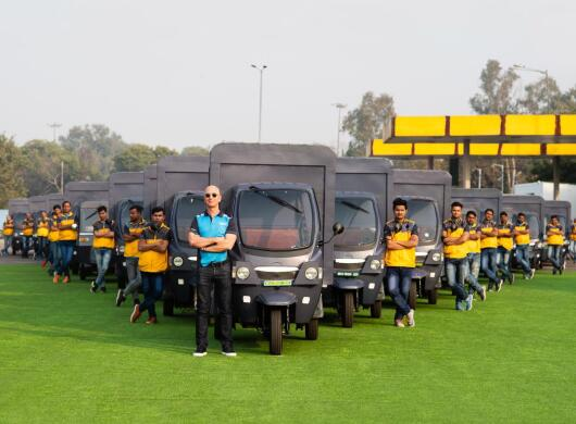 Jeff Bezos stands next to an electric rickshaw, behind him stand several other Amazon delivery drivers who also stand next to electric rickshaws.