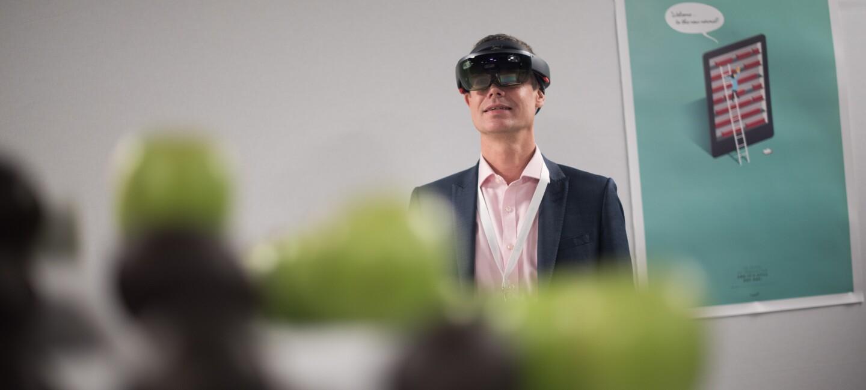 Ein Amazon Mitarbeiter testen eine VR Brille, mit der der Reifegrad von Obst und Gemüse ermittelt werden kann.