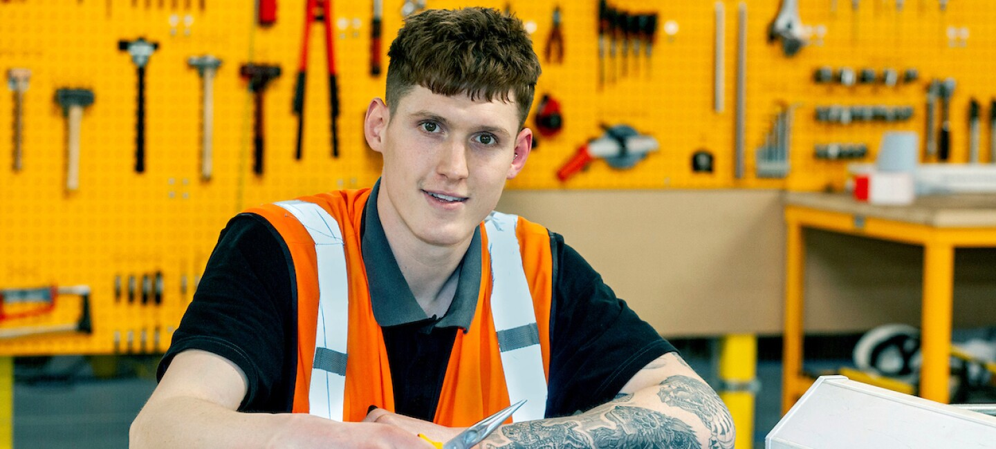 James pictured in a black t-shirt with an orange high visibility vest on top, looking at the camera. He is in a warehouse workshop holding pliers. There are tools on the table in front of him and neatly hanging on the yellow wall behind him.