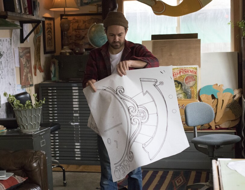 Amazon artist Kyler Martz in his Seattle studio holding a drawing of an upward pointing arrow.