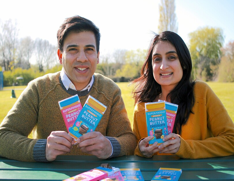 Jagir and Nirali Mankodi, Founders of Superfoodio, sitting at a park bench and holding their products.