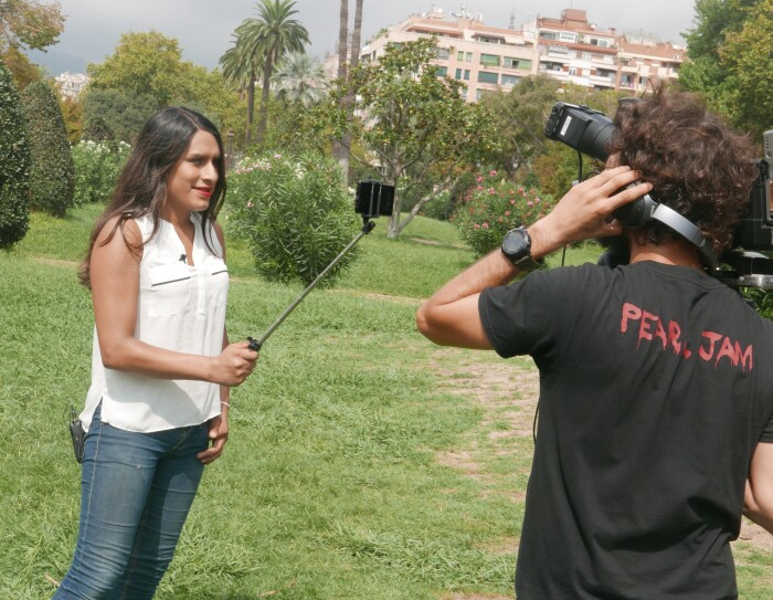 Karla Elena Márquez con unos jeans azules y camisa blanca sujeta un palo selfie . Delante de ella un cámara vestido de negro la enfoca. Están los dos en un parque y se ven arbustos y en el fondo un edificio.