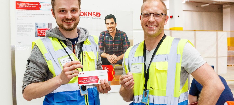 2 Männer mit Sicherheitsweste halten eine DKMS-Karte und ein Wattestäbchen