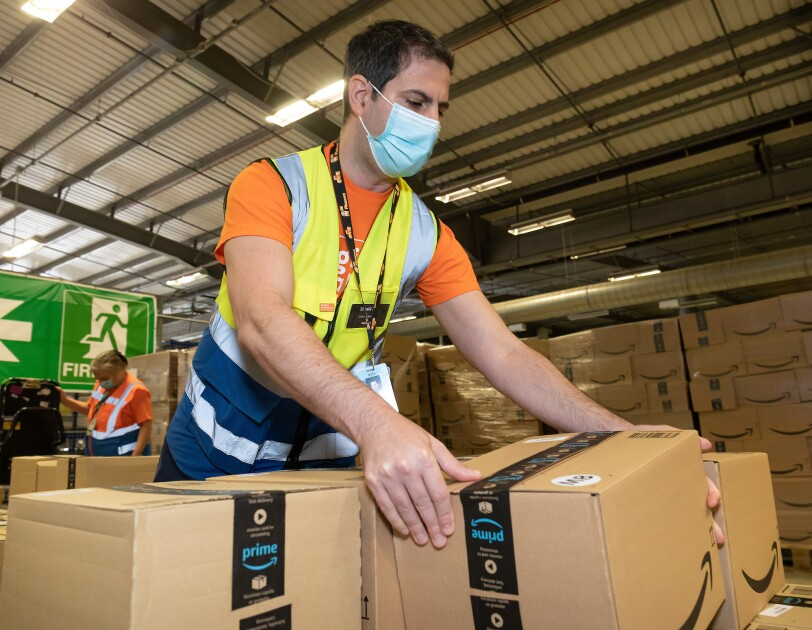 Amazon employee wearing a mask and with boxes for Magic Breakfast delivery