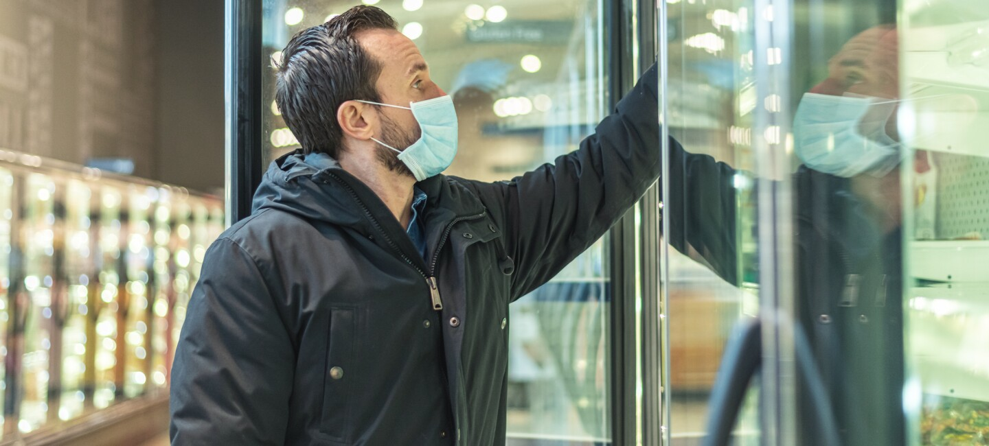 A man wearing a face mask stands at an open frozen foods cooler in a grocery store, reaching in to grab an item.