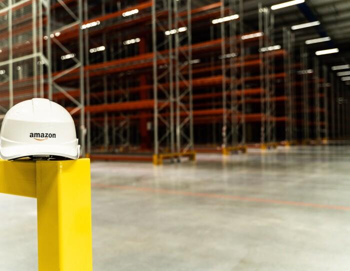 En primer plano aparece un casco de Amazon, de color blanco y con su logo. Está apoyado en una baranda amarilla. De fondo, las estanterías de color rojo.