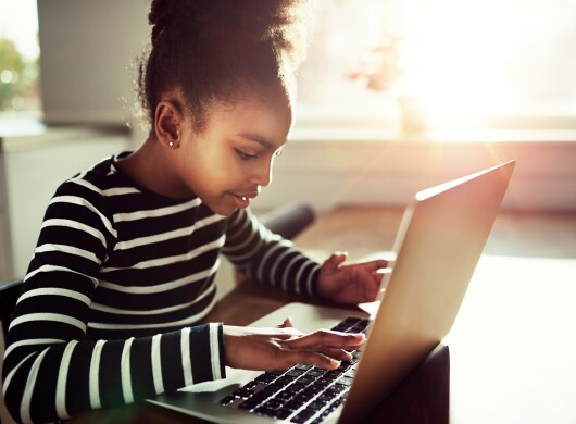 A young girl sits at a table typing on her laptop.