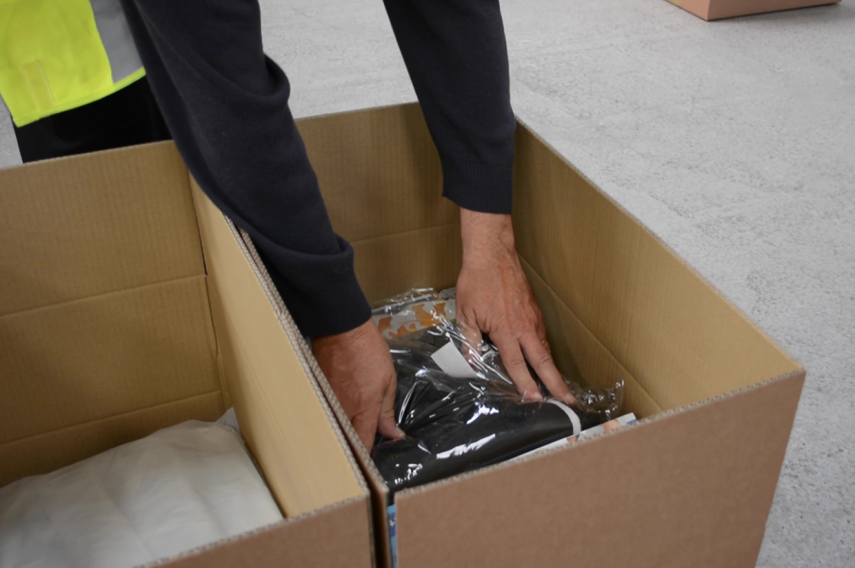 A close up of someones hands packing clothes into an FBA donation package in the UK