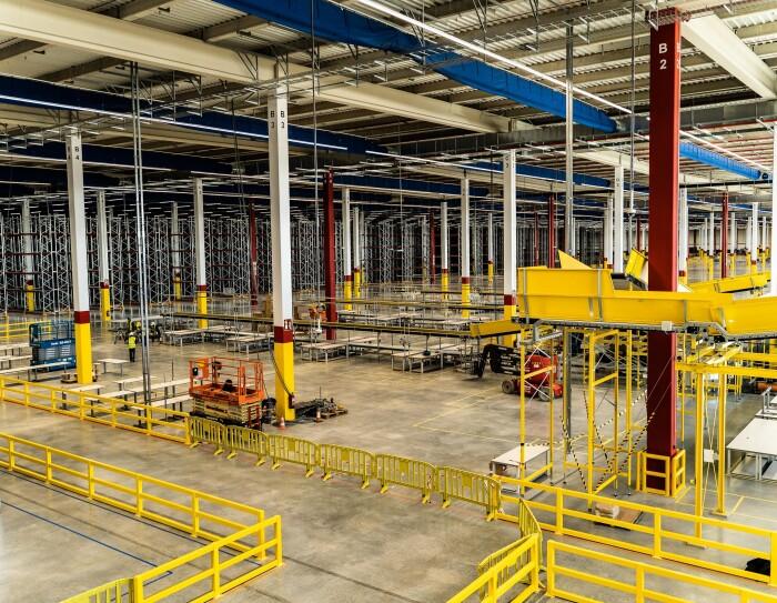 Panorámica del centro logístico de Illescas. Se pueden observar grúas y trabajadores al fondo. En primer plano hay cintas transportadores y en el fondo estanterías para almacenar.