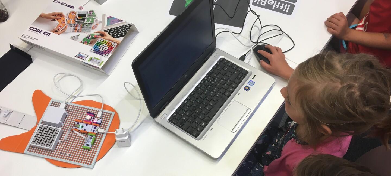 Ein junges Mädchen sitzt am Computer und programmiert. Neben sitzt ein Amazon Mitarbeiter, der ihr hilft und das Programmieren erklärt.