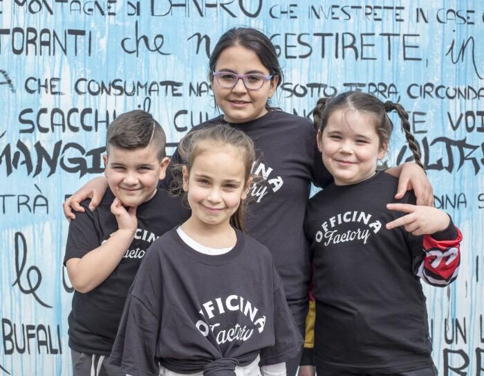 Quattro bambini della biblioteca di Scampia sorridono davanti a un murales