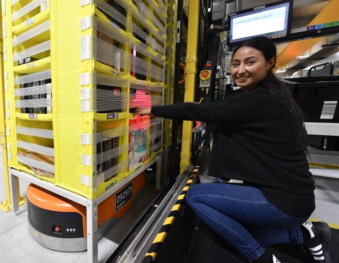 Nachdem der Transportroboter das Regal zu den Mitarbeitern gebracht hat, können Artikel entnommen und für den Versand vorbereitet werden.