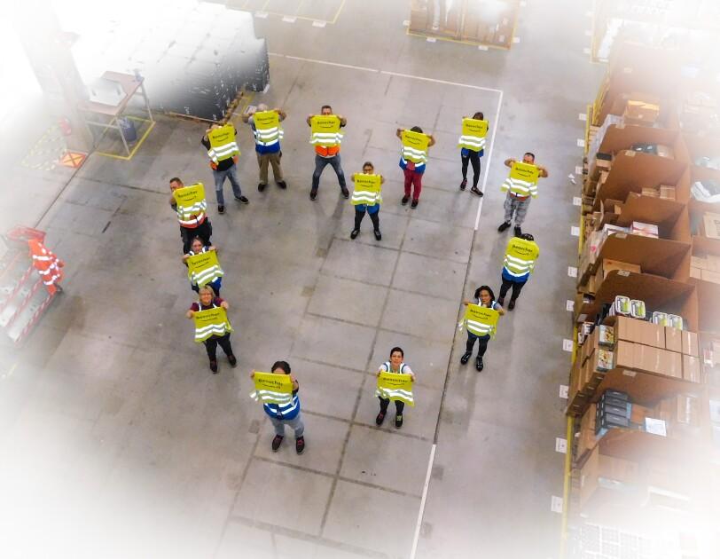Mitarbeiter haben sich in Herzform aufgestellt und halten Besucherwesten vor sich