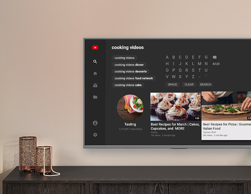A wall-mounted television above a console shows the YouTube experience on Fire TV, with examples of cooking videos.