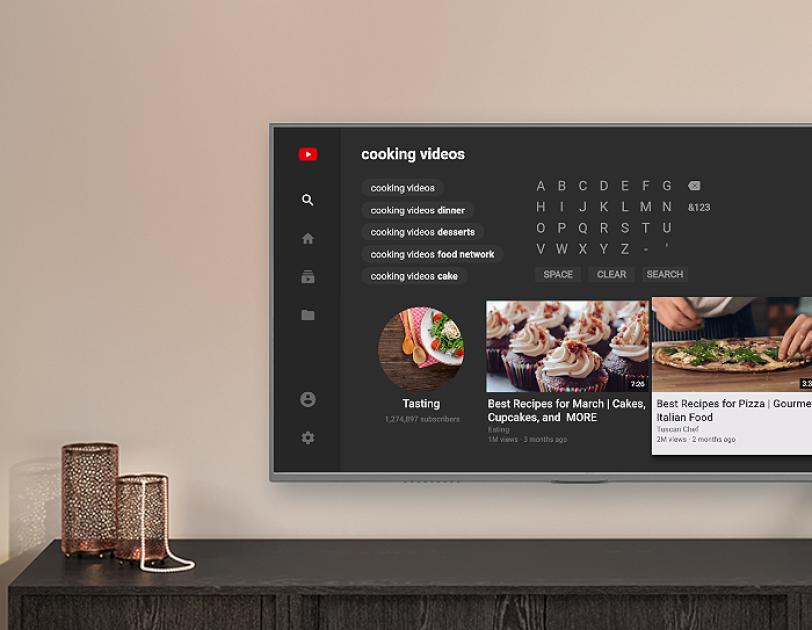Un televisor montado en la pared sobre una consola muestra la experiencia de YouTube en Fire TV, con ejemplos de videos de cocina.
