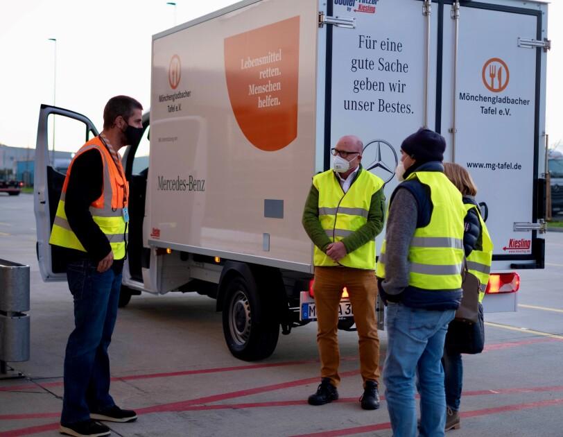 Mitarbeiter von Amazon und der Tafel vor einem Tafel-Lieferwagen.