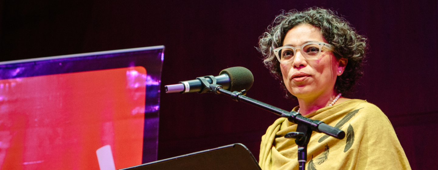 A woman standing at a lecture, in front of a portable podium and microphone. She appears to be speaking to a group, on a stage. In the background, Seattle Arts & Lectures logo is visible.