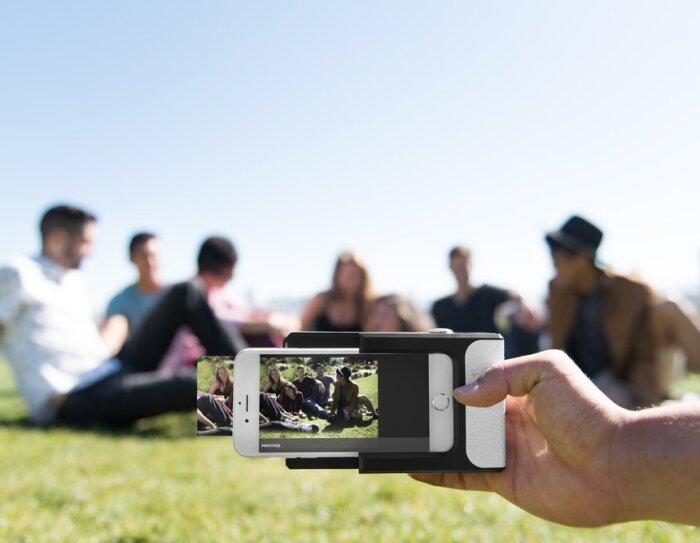 Une main tient une imprimante photo Prynt sur un smartphone, qui est en train d'imprimer la photo d'un groupe de jeunes gens assis dans l'herbe en extérieur