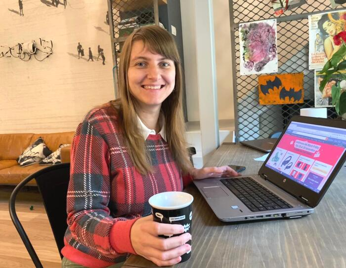 Una donna seduta ad una scrivania davanti ad un pc. Indossa un maglione con fantasia scozzese e in mano regge una tazza nera. Sullo sfondo si intravede un salotto ed una scala.