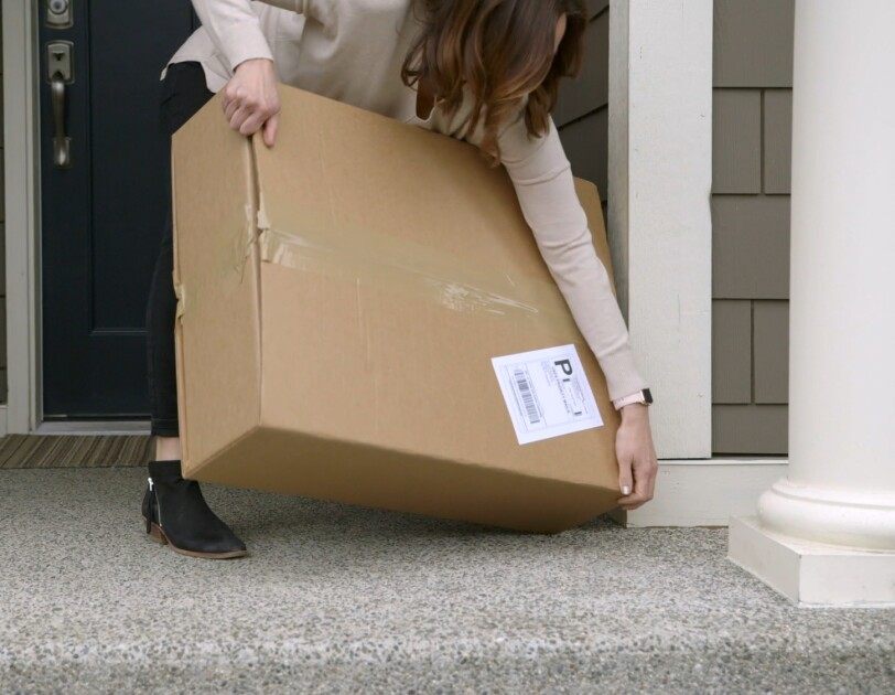 A woman leans down to pick up what appears to be a heavy, bulky cardboard box.