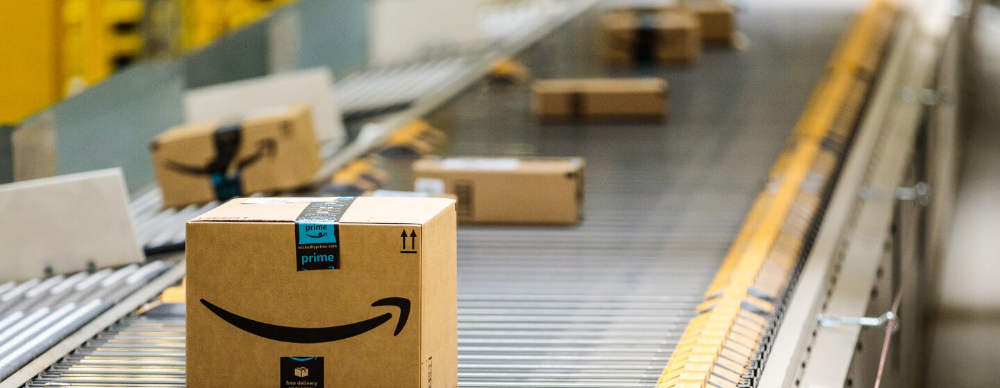Amazon delivery boxes roll down a conveyor belt at Amazon's warehouse in Baltimore, MD.