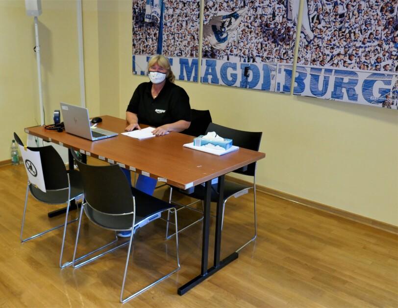 Eine Mitarbeiterin mit Munschutz an einem Tisch.