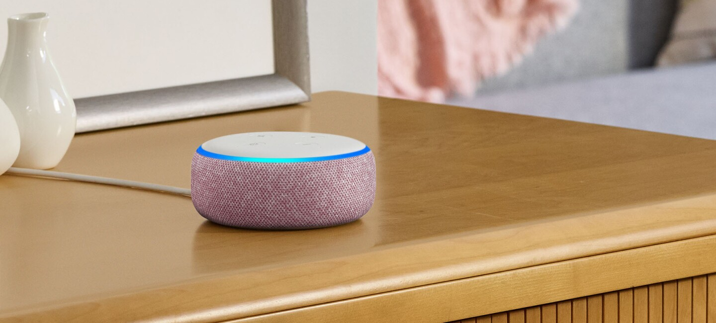 An Echo Dot in plum sits on a bedside table near a print and ceramic vases.